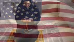 Animation of American flag waving over mixed race woman in hijab