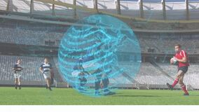 Animation of blue globe spinning with data processing over two multi-ethnic rugby teams playing rugb