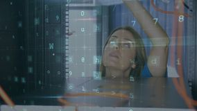 Woman working on a computer server with with moving data security messages. Animation of a Caucasian woman working on computer server seen close up from inside stock footage