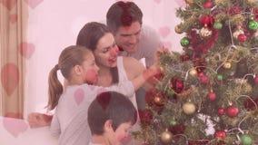 Animation de famille décorant l'arbre de Noël contre du coeur rose banque de vidéos
