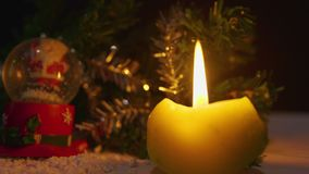 Animation des bougies brûlant et du globe de neige pour le jour de Noël banque de vidéos