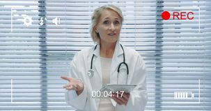 animation of a portrait of a middle aged caucasian female doctor looking to camera holding a tablet computer and talking seen on a stock footage