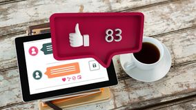 Like symbol and increasing numbers over coffee cup and tablet on table. Animation of red speech bubble with a thumbs up symbol and increasing numbers from zero stock video