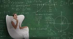 Woman sitting in front of chalkboard with moving calculations on it