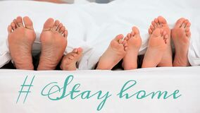 Animation of the words # Stay home over four pairs of bare feet in bed at home.