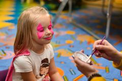 The animator paints a drawing on the face of a little girl at a party.  stock image