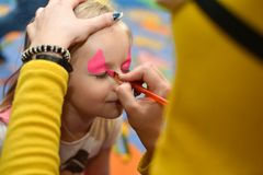 The animator paints a drawing on the face of a little girl at a party.  royalty free stock images