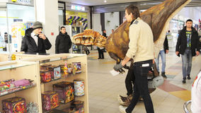 Animator playing a dinosaur and his assistant in the Mall Stock Photo