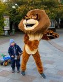 Animatore nei bambini divertenti di un costume del leone nella città dell'argine di Jalta Fotografia Stock Libera da Diritti