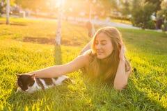 Animaux familiers et concept de propriétaire - belle fille jouant avec un chat dans l'herbe Images stock