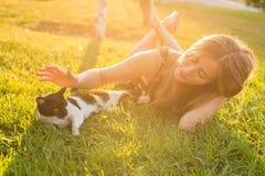 Animaux familiers et concept de propriétaire - belle fille jouant avec un chat dans l'herbe Photographie stock libre de droits