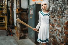 Anime girl with baseball bat in abandoned factory stock photo