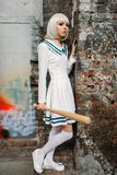 Anime girl with baseball bat in abandoned factory. Anime girl with baseball bat. Cosplay fashion, asian culture, doll in uniform, cute woman with makeup in stock images