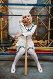 Anime girl with baseball bat, doll in uniform stock photo