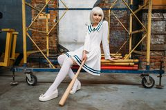 Anime girl with baseball bat, doll in uniform. Pretty anime style blonde girl with baseball bat. Cosplay fashion, asian culture, doll in uniform, cute woman with royalty free stock image