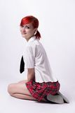 Anime girl in short skirt on a white background. Red-haired girl, style of anime, non-standard, piercings on his face, blue eyes, earrings tunnels, bright stock images