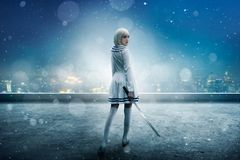 Anime girl on snowy edge of skyscraper roof. Anime style blonde girl with sword on the snowy edge of the skyscraper roof, back view. Cosplay woman, asian culture stock image