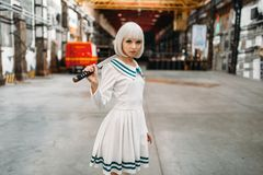Anime girl with sword poses on abandoned factory. Pretty anime style blonde girl with sword poses on abandoned factory. Cosplay fashion, asian culture, doll with royalty free stock image