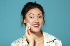 Anime a la muchacha adolescente atractiva limpia su cara con el disco del algodón mañana Imagen de archivo libre de regalías
