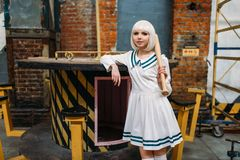 Anime lady with baseball bat n the factory shop. Cute anime style blonde lady with baseball bat. Cosplay fashion, asian culture, doll in dress, woman with makeup royalty free stock photography