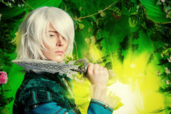 Anime style. Beautiful blond elf with a dagger in his hand in the magic forest. Fantasy. Anime style stock photography