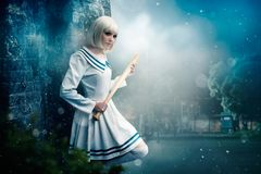 Anime style blonde girl with baseball bat. Pretty anime style blonde girl with baseball bat. Cosplay woman, asian culture, doll with wooden bit in cold tones stock photo