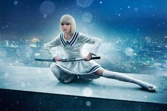 Anime girl with sword on edge of skyscraper roof. Anime style blonde girl with sword on the edge of the skyscraper roof. Cosplay woman, japanese culture, doll stock photo