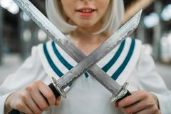 Anime style blonde girl with swords, cute lolita. Anime style blonde girl with two swords, cute lolita. Cosplay fashion, asian culture, doll with blade, pretty stock image