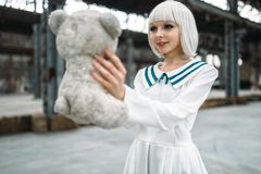 Anime style blonde woman looks at the toy bear. Cosplay girl, japanese culture, doll in dress on abandoned factory royalty free stock images