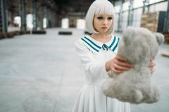 Anime style blonde woman looks at the toy bear. Cosplay girl, japanese culture, doll in dress on abandoned factory royalty free stock photos
