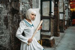 Anime style girl with baseball bat, lolita. Cosplay fashion, asian culture, manga doll in uniform, cute woman with makeup in abandoned factory shop stock images