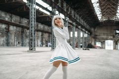 Anime style girl, doll in dress. Anime style girl, blonde woman with makeup. Cosplay, japanese culture, doll in dress on abandoned factory royalty free stock photos