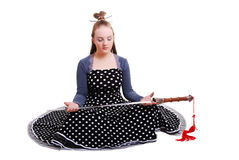 Anime teenage girl holding a sword. Serious teenage girl is sitting and holding a sword in front of herself. Her eyes are closed. She is wearing an anime costume royalty free stock image