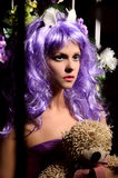 Anime young woman in purple wig with toy Stock Images