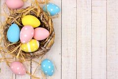 Aninhe a beira lateral com os ovos da páscoa cor-de-rosa, amarelos & azuis contra a madeira branca Fotos de Stock