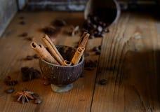 Anis d'étoile, cannelle dans une tasse sur un fond en bois foncé images libres de droits