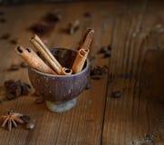 Anis d'étoile, cannelle et d'autres épices dans une tasse sur un fond en bois photographie stock libre de droits