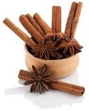 Anis de estrela em uma bacia de madeira com varas de canela em uma parte traseira do branco Imagem de Stock