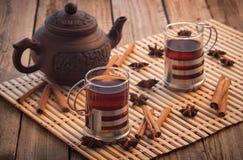 Anis de estrela de madeira da canela da tabela dos vidros de vidro do chá preto imagem de stock