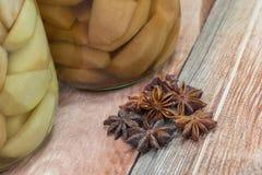 Anis et clous de girofle d'étoile sur le fond en bois avec la poire conservée C Image libre de droits