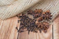 Anis et clous de girofle d'étoile sur le jute sur le fond en bois Photo libre de droits
