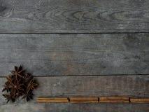 Anis och kanelbruna pinnar på träbakgrund Royaltyfri Fotografi