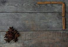 Anis och kanelbruna pinnar på träbakgrund Arkivbild