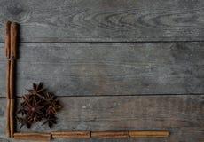Anis och kanelbruna pinnar på träbakgrund Arkivfoto