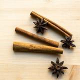 Anis och pinnar av kanel på träbakgrund Kryddor för kaffe, varmt te, funderat vin, stansmaskin royaltyfria foton