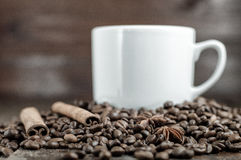 Anis star, cinnamon sticks and coffee grains with cup. On dark background royalty free stock images