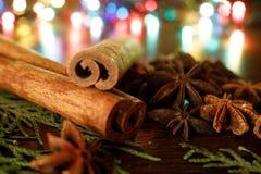 Anis und Zimtstangen auf einem Holztisch mit buntem Höhepunkt Selektiver Fokus Hintergrund für Grußkarte des neuen Jahres lizenzfreie stockfotografie