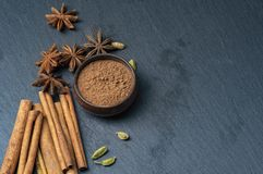 Anise, Cardamom and cinnamon. Brown star anise and cinnamon on a dark background. Ground cinnamon in a cup. Cardamom royalty free stock images