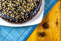 Anise with piece of chocolate cake. Anise and piece of chocolate cake on blue and wooden background Stock Images
