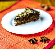 Anise with piece of chocolate cake. Anise and piece of chocolate cake on red background Royalty Free Stock Photos
